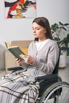 Mulher jovem e atraente com deficiência sentada sob o xadrez na cadeira de rodas lendo um livro em casa