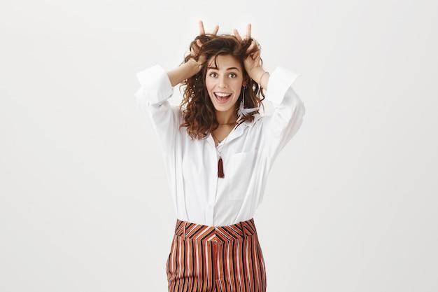 Mulher jovem e atraente com humor brincalhão mostrando orelhas de coelho na cabeça