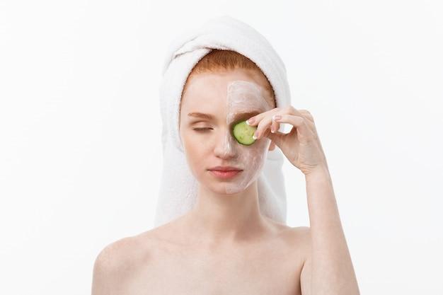 Mulher jovem e atraente com linda pele limpa. máscara branca e pepinos. tratamentos de beleza e terapia de spa de cosmetologia.