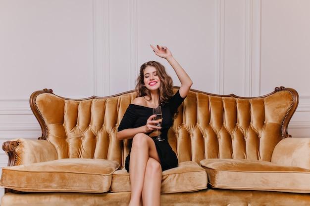 Mulher jovem e atraente, com longos cabelos cacheados e lindos olhos escuros, sorrindo alegremente, segurando uma garrafa de espumante nas mãos