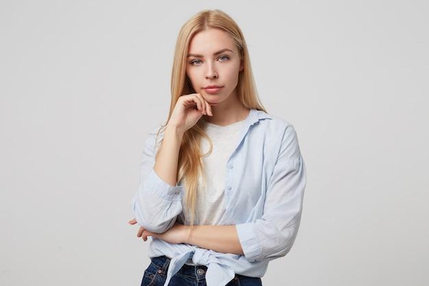 Mulher jovem e atraente com longos cabelos loiros, usando roupas casuais, em pé, olhando séria e segurando o queixo
