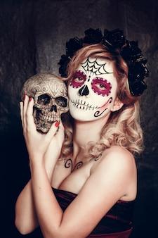 Mulher jovem e atraente com maquiagem de caveira de açúcar. dia mexicano da mulher morta usando maquiagem de caveira de açúcar e grinalda da flor.