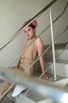 Mulher jovem e atraente com maquiagem e penteado posando sentada na escada