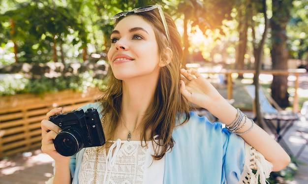 Mulher jovem e atraente com roupa de moda de verão, estilo hippie, vestido branco, capa azul, óculos de sol, sorrindo, segurando uma câmera fotográfica vintage, acessórios elegantes, relaxando nas férias, roupas da moda