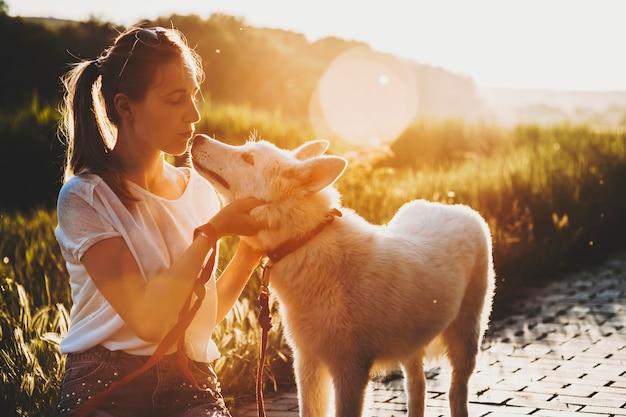 Mulher jovem e atraente com roupas de verão com rabo de cavalo, sentada com os olhos fechados na calçada e beijando o focinho de seu cachorro parado nas proximidades ao pôr do sol em fundo iluminado