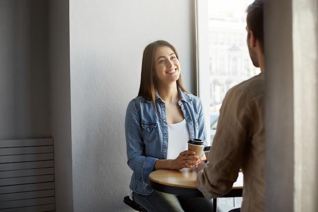 Mulher jovem e atraente com roupas elegantes em um encontro na cafeteria, ouvindo seu parceiro com expressão feliz e animada. estilo de vida, conceito de relacionamento.