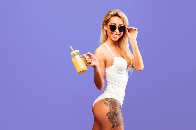 Mulher jovem e atraente com suco de laranja em um frasco na parede roxa.