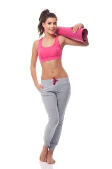 Mulher jovem e atraente com tapete de exercícios
