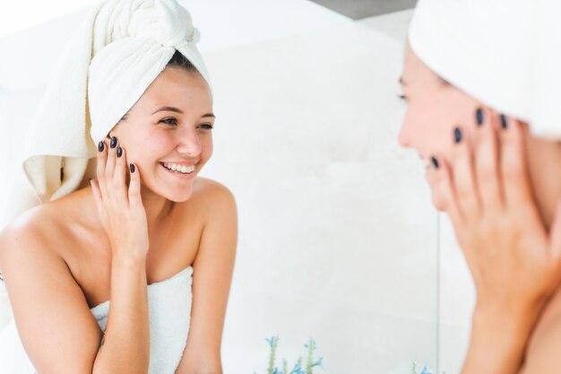 Mulher jovem e atraente com toalha branca na cabeça e corpo com reflexo no espelho do banheiro