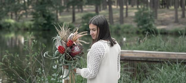 Mulher jovem e atraente com um buquê de flores na floresta à beira do rio