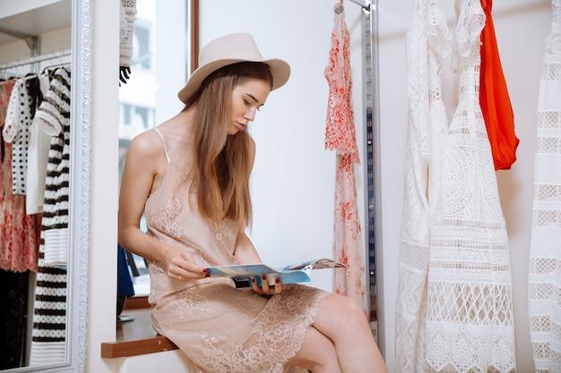 Mulher jovem e atraente com um chapéu sentado e lendo uma revista em uma loja de roupas