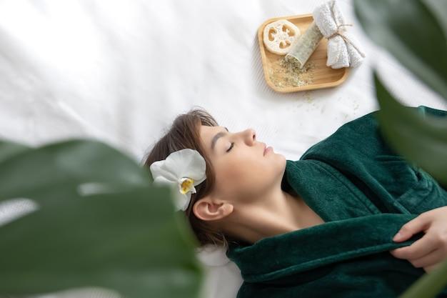 Mulher jovem e atraente com um manto verde encontra-se no salão spa, vista superior.