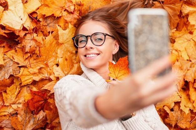 Mulher jovem e atraente com um sorriso fofo se fotografa ao telefone com uma folha de bordo laranja. menina feliz hippie com um suéter e óculos fazendo selfie enquanto está deitada na folhagem laranja ao ar livre