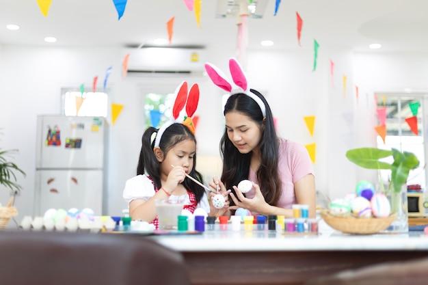 Mulher jovem e atraente com uma linda garotinha estão se preparando para a celebração da páscoa.