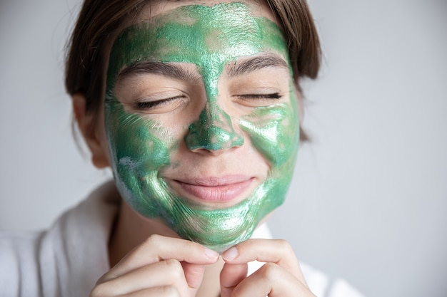 Mulher jovem e atraente com uma máscara cosmética verde no rosto e um manto branco