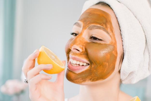 Mulher jovem e atraente com uma toalha branca na cabeça e com máscara marrom facial de lama morde um limão e sorri. cuidados de beleza, spa, pele e corpo.