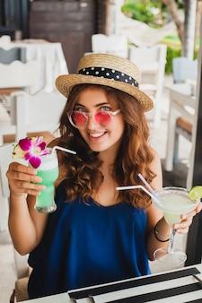 Mulher jovem e atraente com vestido azul e chapéu de palha usando óculos de sol rosa, bebendo coquetéis de álcool nas férias tropicais e sentada à mesa no bar