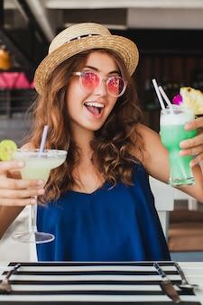 Mulher jovem e atraente com vestido azul e chapéu de palha usando óculos de sol rosa, bebendo coquetéis de álcool nas férias tropicais, sentada à mesa em um bar com roupa estilo verão, sorrindo feliz em clima de festa
