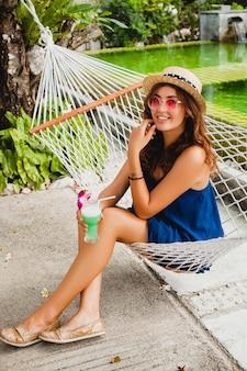 Mulher jovem e atraente com vestido azul e chapéu de palha usando óculos de sol rosa, bebendo um coquetel de álcool e sentada na rede