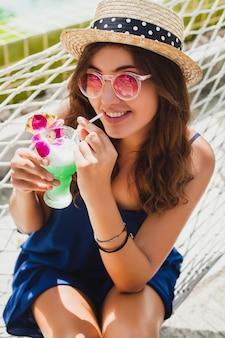 Mulher jovem e atraente com vestido azul e chapéu de palha usando óculos de sol rosa, bebendo um coquetel de álcool nas férias e sentada na rede