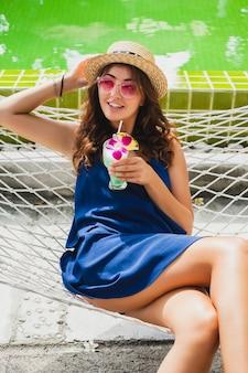 Mulher jovem e atraente com vestido azul e chapéu de palha usando óculos de sol rosa, bebendo um coquetel de álcool nas férias, sentada na rede com roupa estilo verão, sorrindo feliz em clima de festa