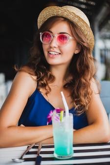 Mulher jovem e atraente com vestido azul e chapéu de palha usando óculos de sol rosa, bebendo um coquetel de álcool nas férias tropicais e sentada à mesa no bar