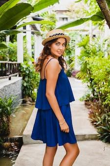 Mulher jovem e atraente com vestido azul e chapéu de palha usando óculos de sol rosa caminhando no hotel tropical spa villa de férias com roupa estilo verão, sexy