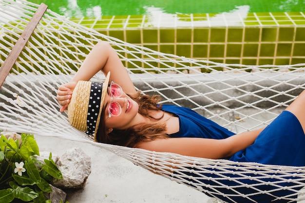 Mulher jovem e atraente com vestido azul e chapéu de palha usando óculos de sol rosa relaxando nas férias deitada na rede com roupa estilo verão, sorrindo feliz