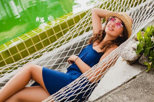 Mulher jovem e atraente com vestido azul e chapéu de palha usando óculos de sol rosa relaxando nas férias deitada na rede