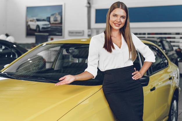 Mulher jovem e atraente concessionária em um showroom perto de um carro novo