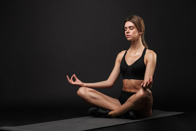 Mulher jovem e atraente, confiante e saudável, vestindo sutiã esportivo e shorts isolados sobre um fundo preto, exercitando-se em uma esteira de fitness, meditando
