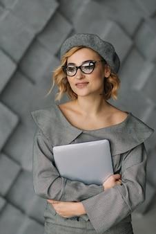 Mulher jovem e atraente confiante em roupas elegantes e óculos, segurando um laptop nas mãos dela. o conceito de mulheres fortes. foco suave.