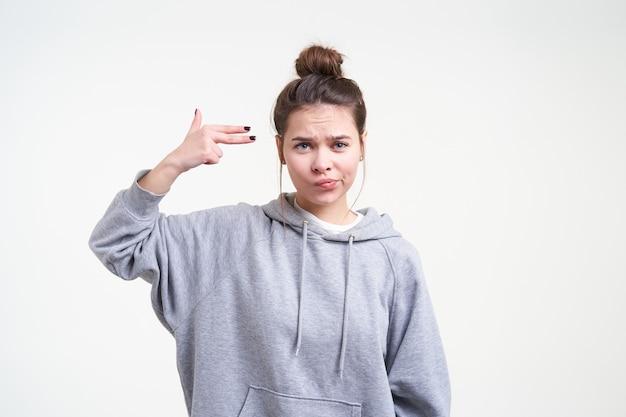 Mulher jovem e atraente confusa de cabelos castanhos imitando a arma com a mão levantada e levantando-a na direção da têmpora enquanto está de pé sobre um fundo branco em roupa casual