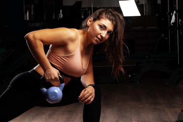 Mulher jovem e atraente curvilínea malhando com halteres em uma academia, escuro