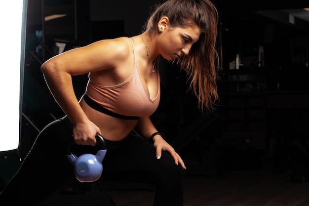 Mulher jovem e atraente curvilínea malhando com halteres em uma academia