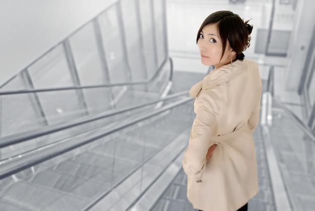 Mulher jovem e atraente de asiático dentro de um edifício moderno.