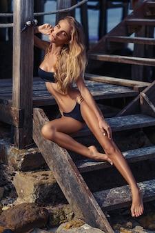 Mulher jovem e atraente de biquíni preto posando para a câmera enquanto está sentada nos degraus de madeira