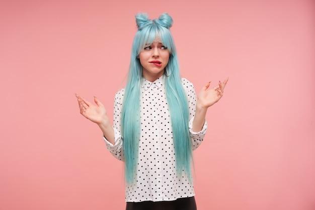 Mulher jovem e atraente de cabelo azul confuso, franzindo a testa e mordendo desconcertantemente o lábio inferior, mantendo as palmas das mãos levantadas enquanto está de pé