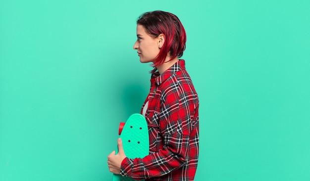 Mulher jovem e atraente de cabelo ruivo em vista de perfil, olhando para copiar o espaço à frente, pensando, imaginando ou sonhando acordada e segurando uma prancha de skate