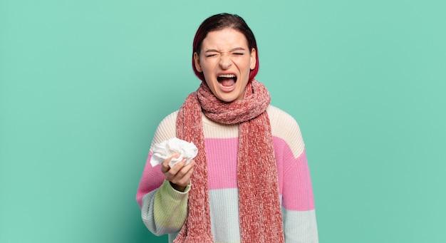 Mulher jovem e atraente de cabelo ruivo gritando agressivamente, parecendo muito zangada, frustrada, indignada ou irritada, gritando sem conceito de gripe