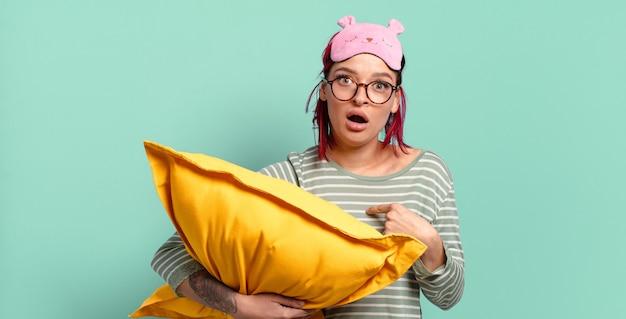 Mulher jovem e atraente de cabelo ruivo parecendo chocada e surpresa com a boca bem aberta, apontando para si mesma e de pijama
