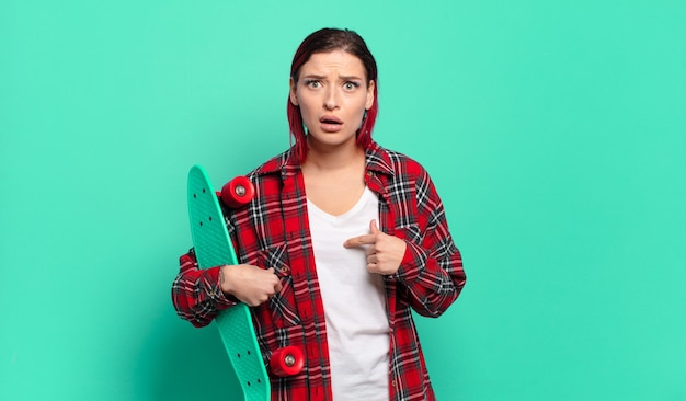 Mulher jovem e atraente de cabelo ruivo parecendo chocada e surpresa com a boca bem aberta, apontando para si mesma e segurando uma prancha de skate