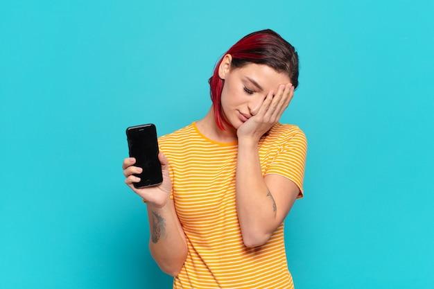 Mulher jovem e atraente de cabelo ruivo se sentindo entediada, frustrada e com sono depois de uma tarefa cansativa, enfadonha e tediosa, segurando o rosto com a mão e mostrando o celular