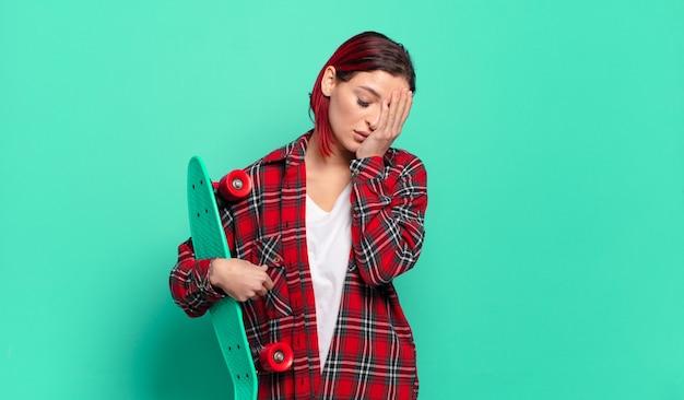 Mulher jovem e atraente de cabelo ruivo se sentindo entediada, frustrada e com sono depois de uma tarefa cansativa, enfadonha e tediosa, segurando o rosto com a mão e segurando uma prancha de skate