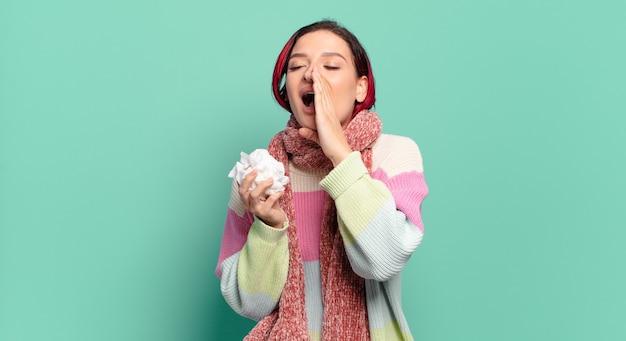 Mulher jovem e atraente de cabelo ruivo se sentindo feliz, animada e positiva, dando um grande grito com as mãos perto da boca, convocando o conceito de gripe