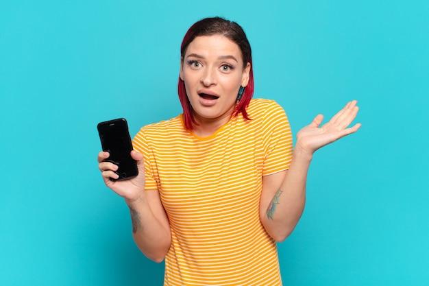 Mulher jovem e atraente de cabelo ruivo se sentindo feliz, animada, surpresa ou chocada segurando um smartphone