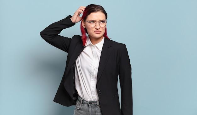 Mulher jovem e atraente de cabelo ruivo se sentindo perplexa e confusa, coçando a cabeça e olhando para o lado