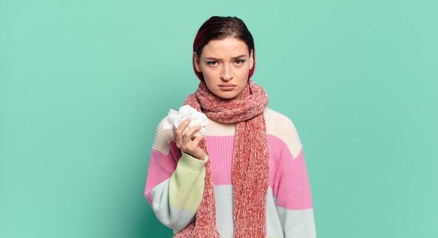 Mulher jovem e atraente de cabelo ruivo se sentindo triste, chateada ou com raiva e olhando para o lado com uma atitude negativa, franzindo a testa em desacordo com o conceito de gripe