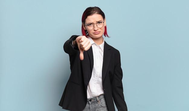 Mulher jovem e atraente de cabelo ruivo se sentindo zangada, irritada, decepcionada ou descontente, mostrando os polegares para baixo com um olhar sério
