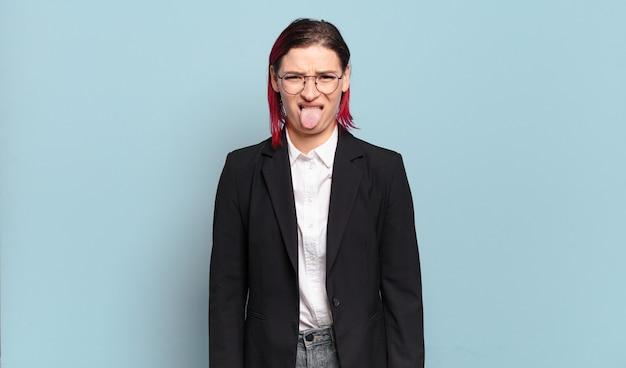Mulher jovem e atraente de cabelo ruivo sentindo-se enojada e irritada, mostrando a língua, não gostando de algo nojento e nojento